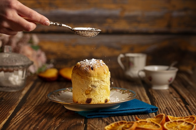 Маленький торт в тарелке на деревянном столе