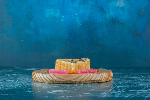 A small cake and marmelades on a wooden platter on blue background. high quality photo