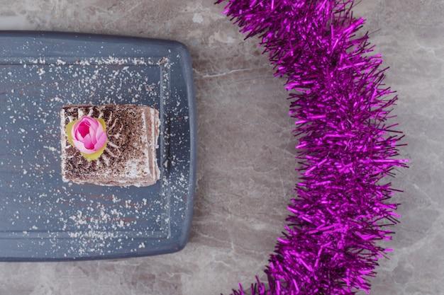 Una piccola fetta di torta su una tavola accanto a una ghirlanda di marmo