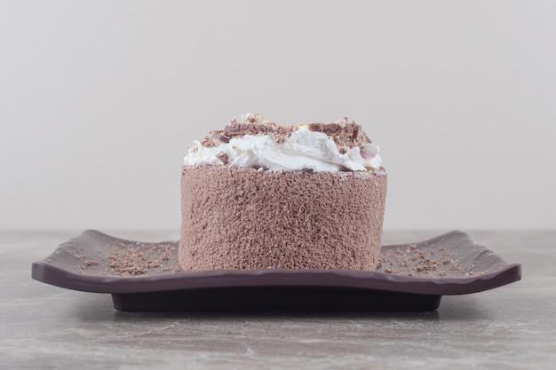 大理石の大皿にみじん切りのオレンジをトッピングした小さなケーキ