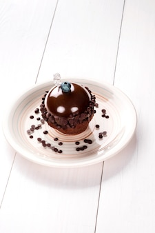 Small cake with different stuffing on a white plate. white wooden table. still life. copy space