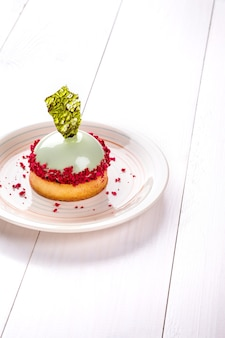 Small cake with different stuffing on a white plate white wooden table