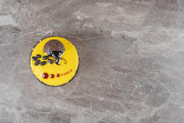 Una piccola torta con rivestimento al gusto di limone su superficie di marmo