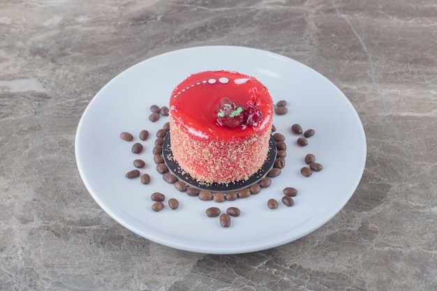 대리석 표면의 플래터에 딸기 시럽 토핑과 커피 콩을 넣은 작은 케이크