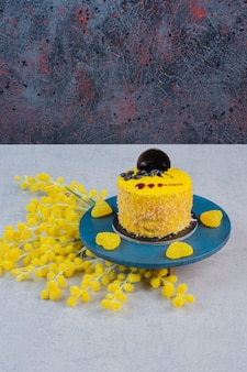 Small cake and yellow heart shaped candies on blue plate.