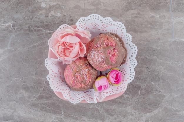 大理石のドイリーで覆われたボウルに小さなケーキと花の花冠