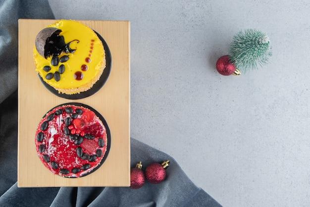 Piccole torte su una tavola con decorazioni natalizie su sfondo marmo.