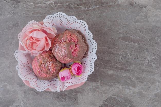 Pasticcini e corolle di fiori in una ciotola ricoperta di centrini su marmo