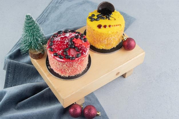 大理石の背景にクリスマスの装飾が施されたボード上の小さなケーキ。