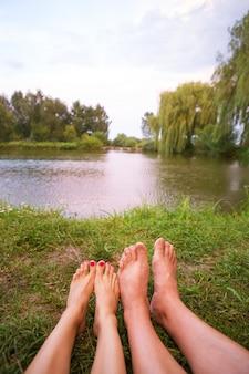 Небольшая палатка на берегу озера, ночлег и ноги молодой пары