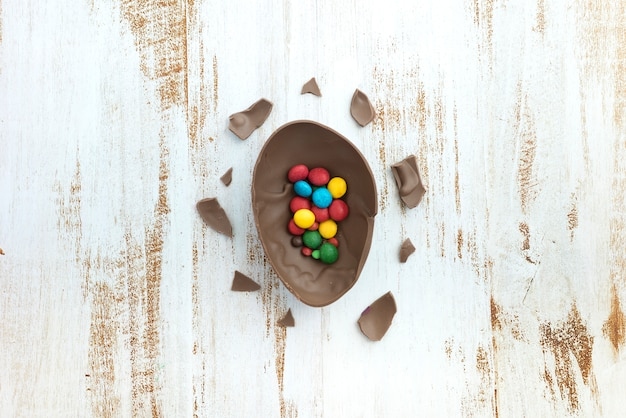 Small candies in open chocolate egg on table