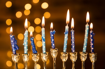 Small candles of menorah near abstract lights