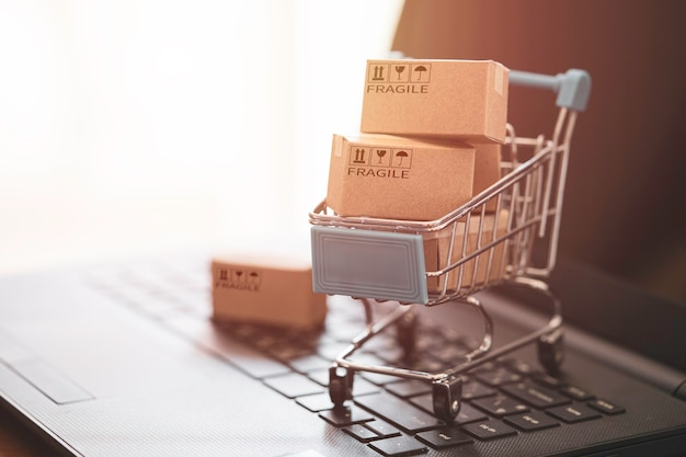 オンラインショッピングの概念のためのコンピュータのラップトップ上のショッピングトロリーと小さなカートンボックス。