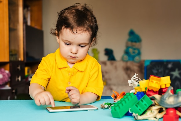 Small caucasian baby boy uses smartphone at home