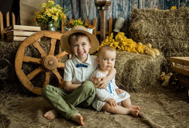 Маленькие кавказские брат и сестра сидят на соломе в пасхальном украшении со стогом сена и утятами. пасха для детей