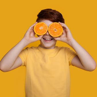 Маленький кавказский рыжий мальчик закрывает глаза апельсинами, позирует в футболке на желтой стене со свободным пространством
