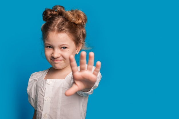 Маленькая кавказская девушка показывает знак остановки и улыбается в камеру, позируя на синей стене студии со свободным пространством