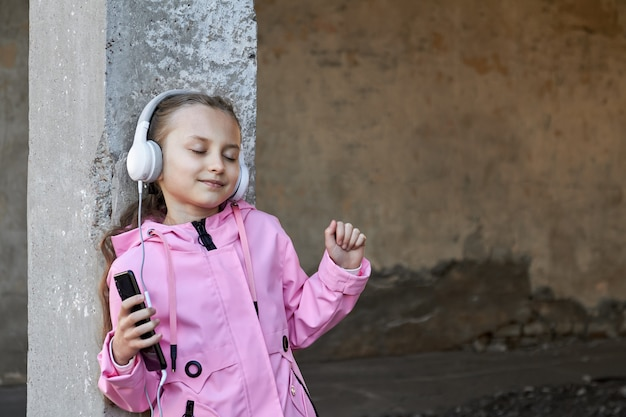 Small caucasian girl in pink cloak is listening to music in headphones against concrete wall. girl dancing with her eyes closed. enjoy the music. wireless headphones