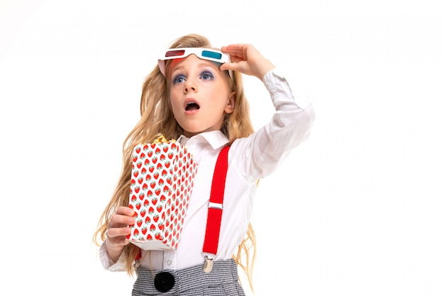 Small caucasian girl with makeup and long blonde hair with pop-corn and 3d glasses is shocked