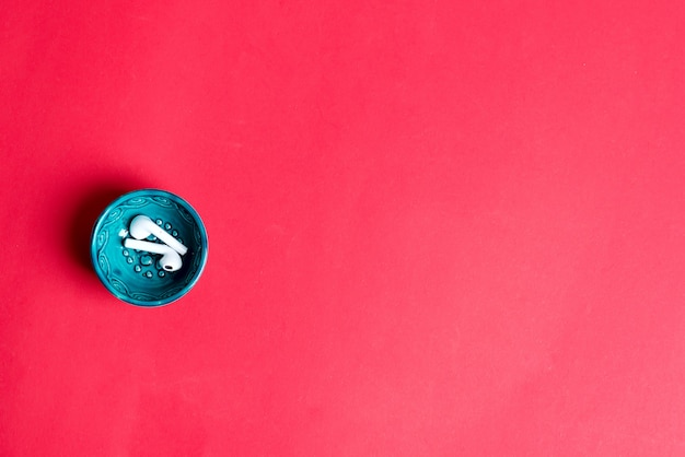 Small ceramic plate with wireless earphones on a red background. top view. daily accessories for modern life.
