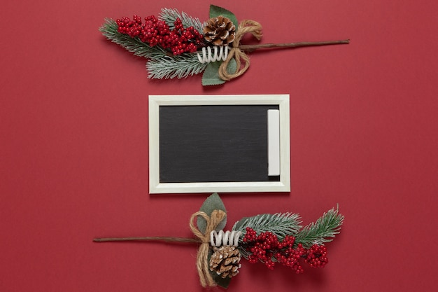 Small chalk board, frame of spruce and berries with copy space on dark red background