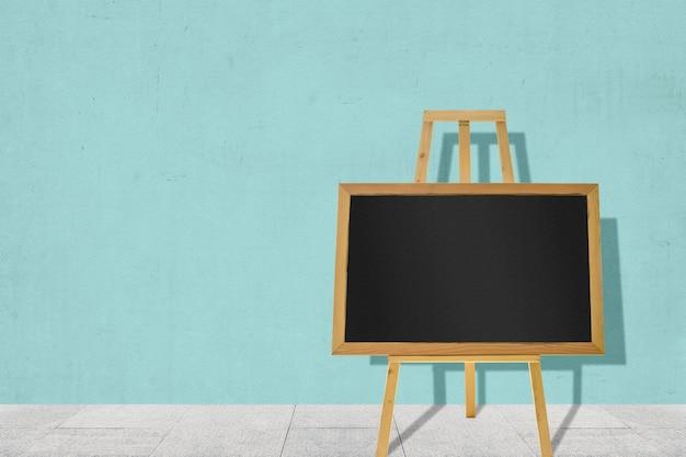 Маленькая доска на деревянном мольберте с цветным стенным фоном. пустая доска для копирования пространства
