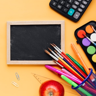 Small chalkboard with bright stationery on beige background