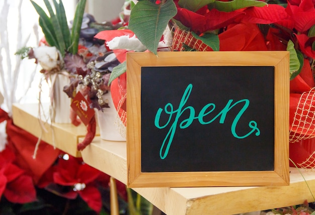 Small chalkboard with text open inside a flower shop during christmas holiday season