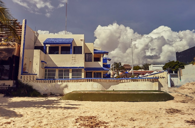Small characteristic white and blue cottage on the beach of playa del carmen in mexico.