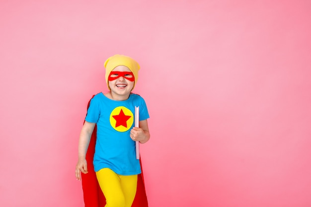 Small cheerful child playing a superhero with a red cape and a star, with a book