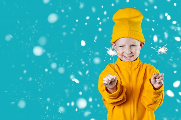 A small cheerful child in a yellow hat and jacket holds burning sparklers
