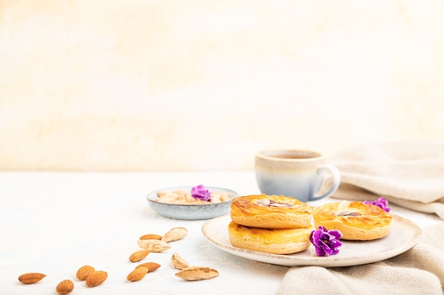 白いコンクリートの上にジャムとアーモンドとコーヒーのカップと小さなチーズケーキ