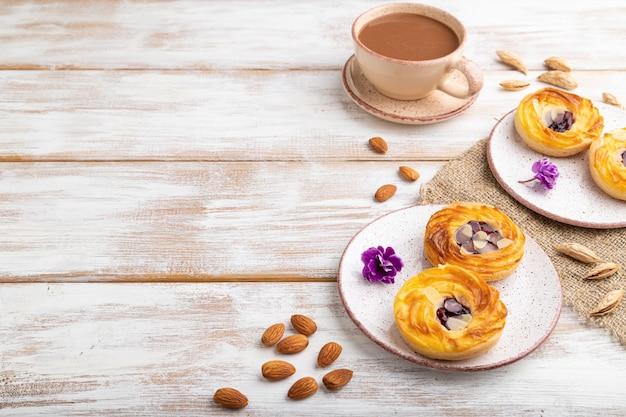 白い木製の上のコーヒーのカップとジャムとアーモンドの小さなチーズケーキ