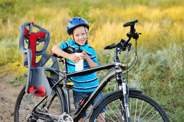 Маленький ребенок-мальчик в велосипедном шлеме с бутылкой воды в руках улыбается, держа большой взрослый горный велосипед с детским велосипедным сиденьем на фоне поверхности природы