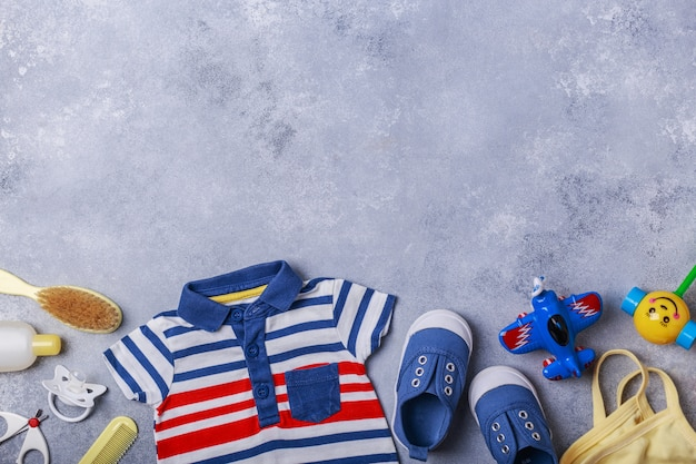 Small child or baby boy accessories on grey surface travel with baby concept