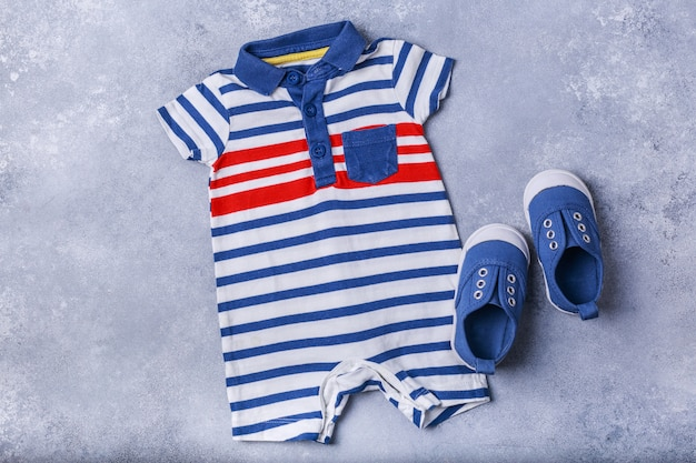 Small child or baby boy accessories on grey surface