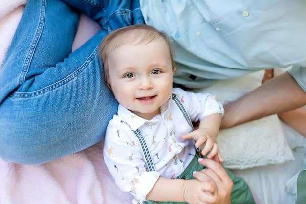 Маленький ребенок мальчик 1 год лежал на кровати с отцом, концепция счастливой семьи,