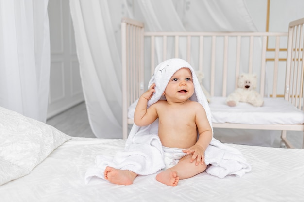 A small child a boy 8 months old is sitting in a towel on a white bed in a light nursery in diapers after bathing