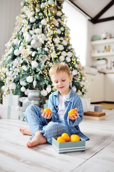 A small child boy in blue pajamas sits barefoot on the warm floor and holds a box of tangerines in the background of a christmas tree.