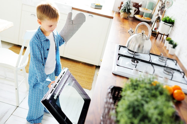 A small child a boy in blue pajamas with a glove stands against the background of an open oven and smiles against the background of the kitchen