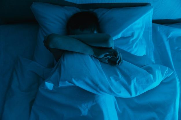 어린 아이 소년은 어두운 밤에 침대에 누워 악몽과 어린이의 끔찍한 꿈을 두려워합니다.
