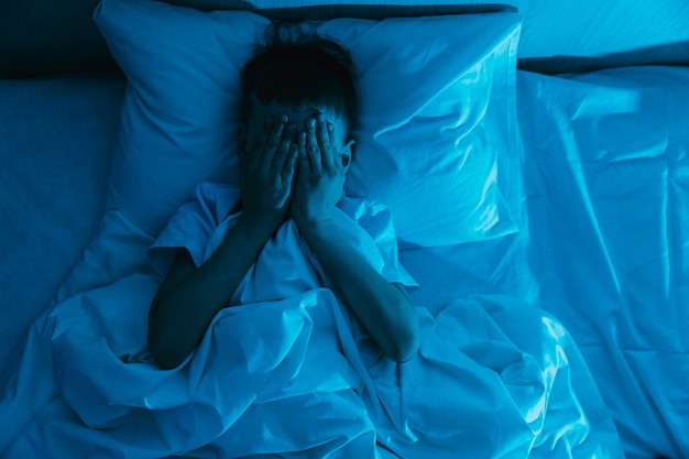 작은 아이 소년은 어두운 밤에 침대에 누워 두려움에 손으로 얼굴을 가리고 어린이의 악몽과 끔찍한 꿈을 두려워합니다.