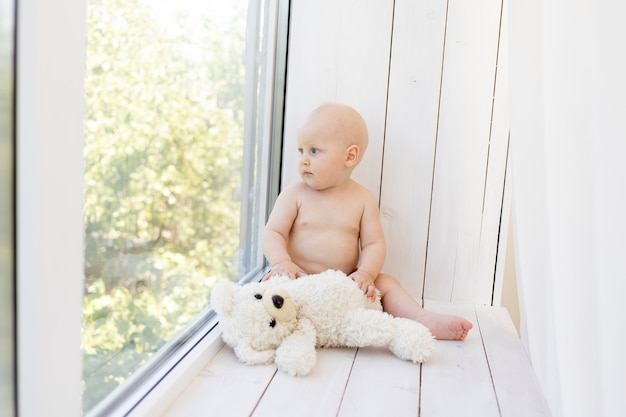 Small child a boy sitting in diapers on the window with soft toys bears