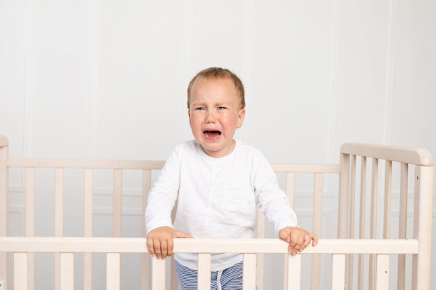 A small child a boy in white pajamas is standing in the crib and crying