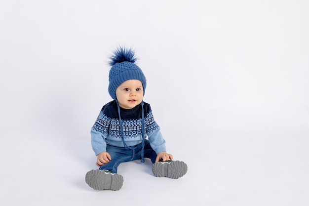 A small child boy in a winter warm hat with a pompom and a blue jacket sits on white