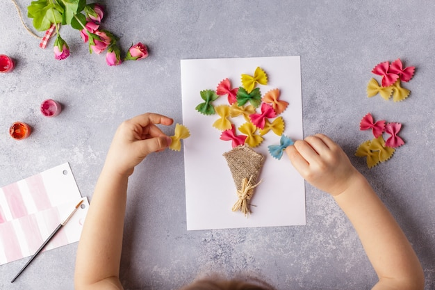 Small child doing a bouquet of flowers out of colored paper and colored pasta.