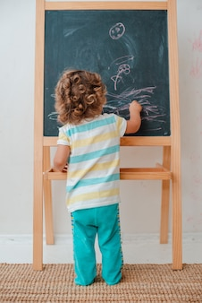 Small child draws with chalk on a black chalk board at home in the nursery against a gray wall.