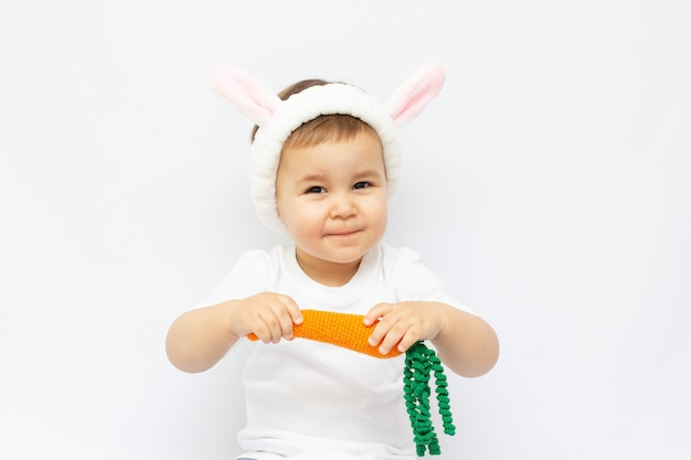 A small child dressed as a rabbit with a carrot