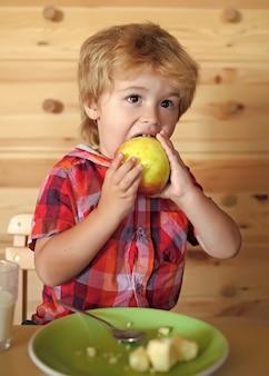 작은 아이가 사과를 먹는다. 건강한 어린이 음식과 비타민. 아침, 아침 가족.