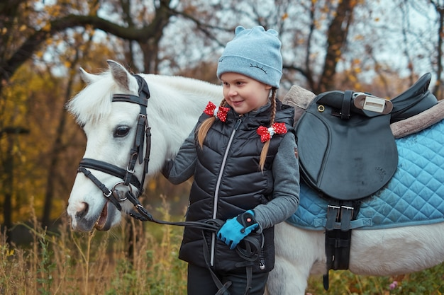 Маленькая девочка и пони лошадь изолированы на открытом воздухе